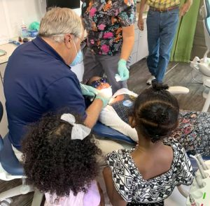 A dentist cleaning a child's teeth while two other children watch